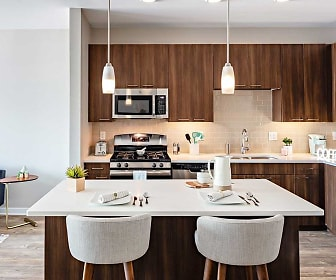kitchen featuring gas range oven, stainless steel appliances, dark brown cabinets, light countertops, pendant lighting, and light parquet floors, Avalon Piscataway