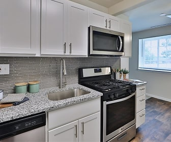 kitchen featuring a ceiling fan, natural light, gas range oven, stainless steel appliances, white cabinets, light stone countertops, and dark hardwood flooring, Knollwood Manor