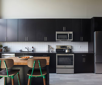 kitchen with stainless steel appliances, electric range oven, light flooring, dark brown cabinetry, and light countertops, Brim & Crown