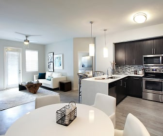 kitchen with a ceiling fan, plenty of natural light, electric range oven, refrigerator, dishwasher, stainless steel microwave, light hardwood floors, pendant lighting, dark brown cabinetry, and light countertops, Legacy Naples