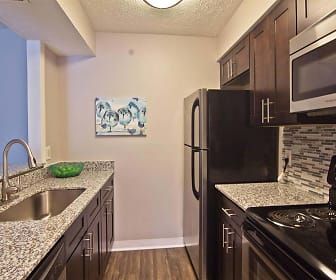kitchen featuring stainless steel microwave, refrigerator, dishwasher, dark brown cabinetry, light granite-like countertops, and dark hardwood floors, Camelot East