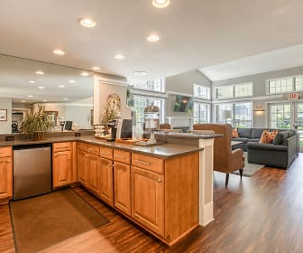 kitchen featuring natural light, TV, stainless steel dishwasher, dark parquet floors, and brown cabinetry, Hunters Glen
