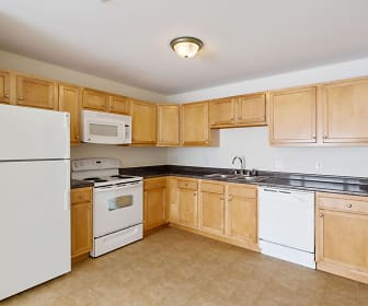 kitchen featuring refrigerator, electric range oven, dishwasher, microwave, dark countertops, light tile floors, and brown cabinets, Legacy Park Apartments