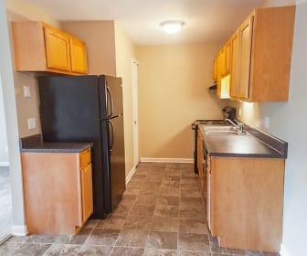 kitchen with range hood, refrigerator, range oven, brown cabinets, dark tile floors, and dark stone countertops, Hunter's Ridge