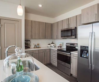 kitchen featuring electric range oven, stainless steel appliances, dark floors, light countertops, pendant lighting, and brown cabinetry, Avalon Southlands