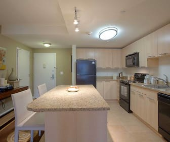 kitchen featuring vaulted ceiling, a center island, microwave, electric range oven, dishwasher, refrigerator, light tile floors, light stone countertops, and light brown cabinetry, Avalon White Plains