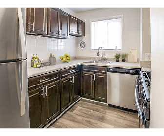 kitchen featuring natural light, stainless steel appliances, range oven, dark brown cabinets, light parquet floors, and light countertops, 101 North Ripley