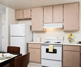 kitchen featuring refrigerator, dishwasher, electric range oven, exhaust hood, light countertops, light brown cabinetry, and light floors, eaves Pacifica