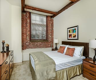 bedroom with wood beam ceiling and exposed bricks, Bigelow Commons
