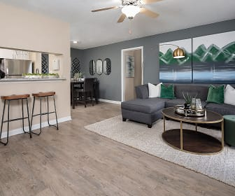 hardwood floored living room featuring a ceiling fan, a kitchen breakfast bar, and refrigerator, The Braxton