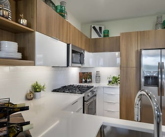 kitchen with stainless steel appliances, gas range oven, dark brown cabinets, and light countertops, Woodbine