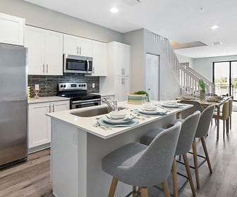 kitchen featuring a breakfast bar, natural light, electric range oven, stainless steel appliances, light countertops, white cabinetry, and light parquet floors, Pines Garden at City Center