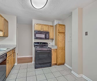 kitchen with refrigerator, gas range oven, dishwasher, microwave, light tile floors, brown cabinets, and light countertops, 2200 Grace
