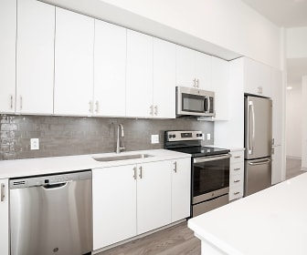 kitchen with stainless steel appliances, electric range oven, white cabinetry, light hardwood floors, and light countertops, Vista Brooklyn