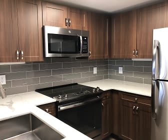 kitchen featuring electric range oven, stainless steel appliances, light flooring, light countertops, and brown cabinetry, Mizner Park