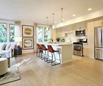kitchen featuring a kitchen bar, a healthy amount of sunlight, stainless steel appliances, range oven, light countertops, pendant lighting, light brown cabinets, and light hardwood flooring, Park Place Apartments
