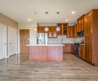 kitchen featuring a kitchen island, stainless steel refrigerator, range oven, microwave, light countertops, pendant lighting, brown cabinets, and light hardwood flooring, Ascend at Woodbury
