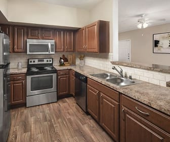 kitchen with a ceiling fan, stainless steel appliances, electric range oven, stone countertops, light parquet floors, and dark brown cabinets, Camden Buckingham