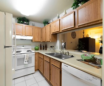 kitchen featuring refrigerator, electric range oven, dishwasher, fume extractor, light countertops, light tile floors, and brown cabinetry, Verandas On The Green