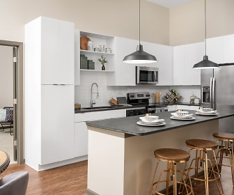 kitchen with stainless steel refrigerator, range oven, microwave, kitchen island sink, light parquet floors, dark countertops, pendant lighting, and white cabinets, The Louis Apartment Flats