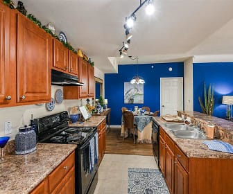 kitchen with electric range oven, dishwasher, extractor fan, light tile floors, stone countertops, pendant lighting, and brown cabinetry, Fountain Villas