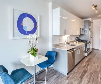 kitchen with range oven, dishwasher, microwave, light hardwood flooring, light stone countertops, and white cabinets, Noca Blu