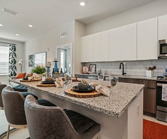 kitchen with a center island, natural light, range oven, stainless steel microwave, white cabinetry, light flooring, and light granite-like countertops, Mirrorton Apartments