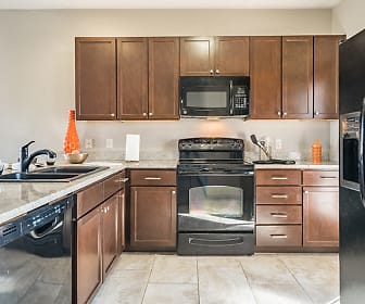 kitchen with refrigerator, electric range oven, dishwasher, microwave, dark brown cabinetry, light tile flooring, and light stone countertops, The Villas at Wilderness Ridge
