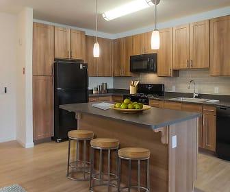 kitchen with a kitchen breakfast bar, microwave, refrigerator, dishwasher, range oven, pendant lighting, dark brown cabinetry, light hardwood floors, and dark countertops, Avalon East Norwalk