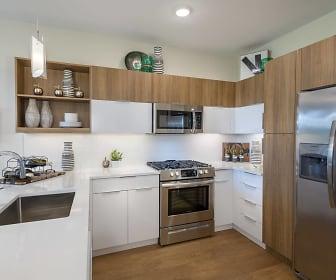 kitchen featuring gas range oven, stainless steel appliances, dark brown cabinets, light countertops, pendant lighting, and light hardwood flooring, Woodbine