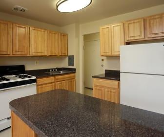 kitchen with gas range oven, baseboard radiator, refrigerator, light flooring, dark granite-like countertops, and brown cabinetry, Laurel Park & Laurelton Court