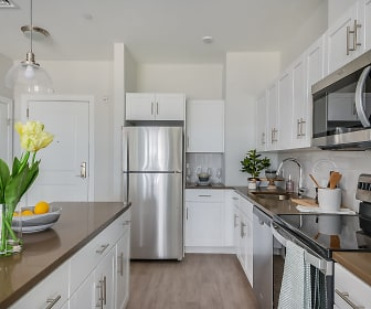kitchen with electric range oven, stainless steel appliances, white cabinets, pendant lighting, and light parquet floors, The Wel