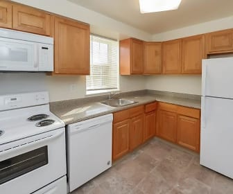kitchen featuring natural light, electric range oven, refrigerator, dishwasher, microwave, light tile floors, stone countertops, and brown cabinets, Woodacres Apartment Homes