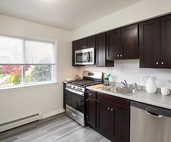 kitchen featuring a healthy amount of sunlight, baseboard radiator, stainless steel appliances, gas range oven, light countertops, light parquet floors, and dark brown cabinets, Westgate Gardens
