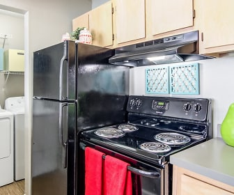 kitchen with electric range oven, refrigerator, extractor fan, separate washer and dryer, light countertops, brown cabinets, and light parquet floors, The Hub Auburn