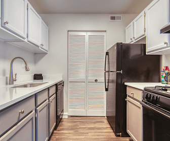 kitchen with gas range oven, refrigerator, fume extractor, light countertops, white cabinetry, and light hardwood flooring, The View