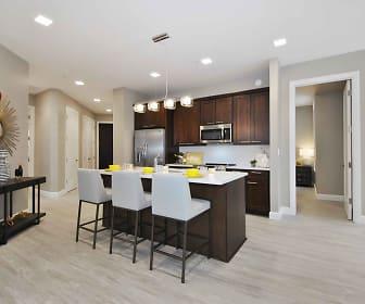 kitchen featuring stainless steel appliances, light flooring, light countertops, kitchen island sink, dark brown cabinetry, and pendant lighting, City Flats