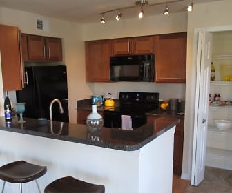 kitchen featuring a kitchen breakfast bar, range oven, refrigerator, microwave, light floors, brown cabinets, and dark stone countertops, TGM Bermuda Island
