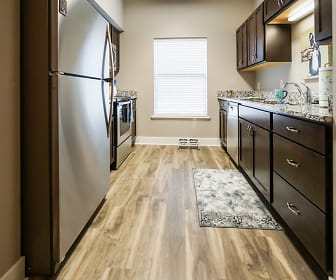 kitchen with natural light, stainless steel refrigerator, range oven, stone countertops, dark brown cabinetry, and light hardwood floors, The Mirada