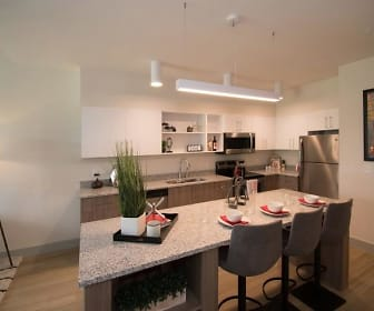kitchen with a breakfast bar area, stainless steel refrigerator, dishwasher, range oven, microwave, white cabinetry, light hardwood floors, and pendant lighting, The Lofts at South Lake