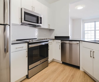 kitchen with natural light, stainless steel appliances, electric range oven, dark countertops, white cabinets, and light hardwood floors, The Landings at Port Imperial