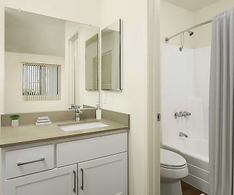 full bathroom featuring vanity, dual mirrors, toilet, shower / washtub combination, and shower curtain, eaves Phillips Ranch