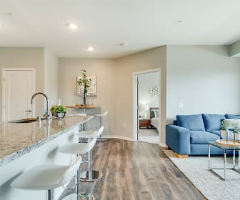 kitchen featuring a breakfast bar, light hardwood flooring, white cabinets, and light granite-like countertops, Ascend at Woodbury