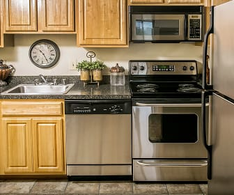 kitchen featuring stainless steel appliances, electric range oven, granite-like countertops, light floors, and brown cabinets, Foxfire Apartments