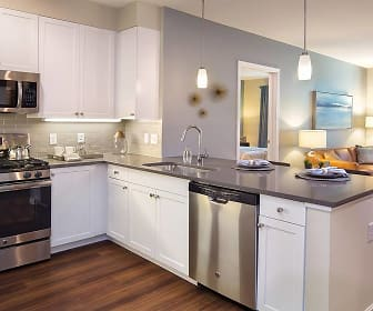 kitchen featuring natural light, gas range oven, stainless steel appliances, dark hardwood flooring, pendant lighting, white cabinetry, and dark countertops, Avalon Quincy
