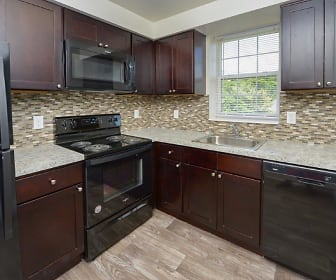 kitchen with natural light, stainless steel appliances, electric range oven, dark brown cabinets, light stone countertops, and light hardwood floors, Woodacres Apartment Homes