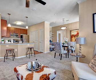 A living room with a ceiling fan and view into the kitchen, Le Mirage