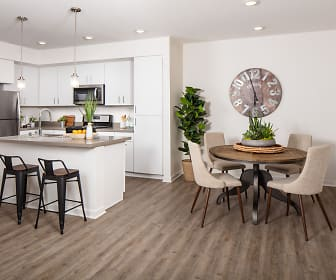 kitchen with a kitchen breakfast bar, stainless steel refrigerator, range oven, microwave, pendant lighting, white cabinets, light parquet floors, and light countertops, Homecoming At Creekside