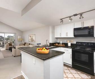 kitchen featuring a center island, carpet, lofted ceiling, electric range oven, microwave, light flooring, white cabinets, and dark stone countertops, Camden Sea Palms