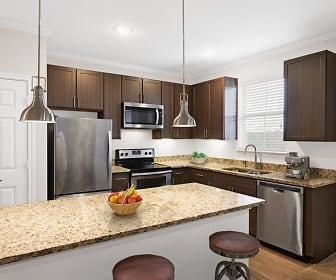 kitchen featuring a breakfast bar, natural light, electric range oven, stainless steel appliances, dark brown cabinetry, light granite-like countertops, pendant lighting, and light parquet floors, Camden Cedar Hills